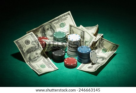 Poker chips and dollar Money bills on green cloth - stock photo