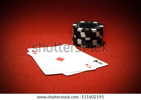 Poker chips and playing cards on red background - stock photo