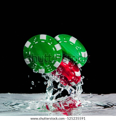 Poker chips falling into the clear water on black background