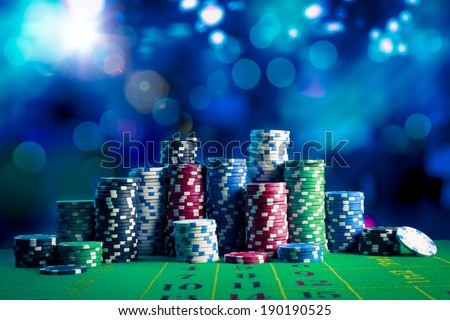 Poker Chips on a gaming table with dramatic lighting - stock photo