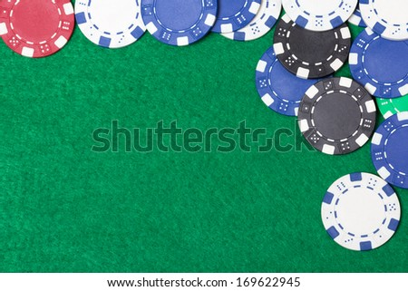 poker chips on a green casino table background - stock photo
