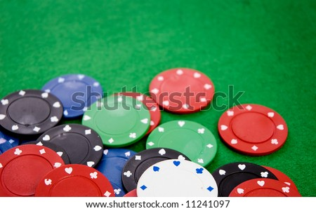 Poker chips on green background. Room for text. Shallow DOF. - stock photo