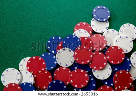 Poker chips on green felt - stock photo