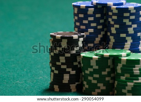 Poker chips, on green felt, with copy space - stock photo