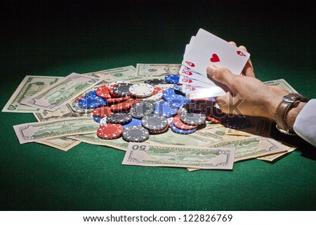 Poker chips, playing cards and cash for gambling concept image