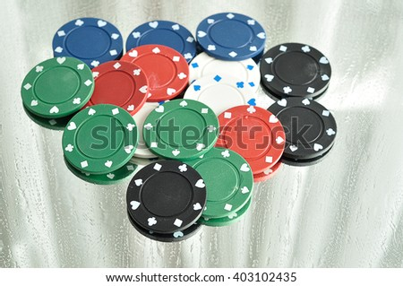 Poker chips reflecting in a mirror that is stained with water drops