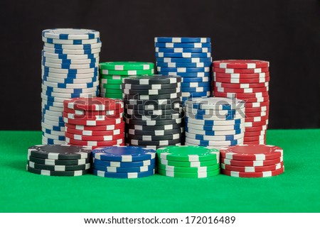 poker chips stack on green table, black background - stock photo