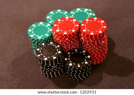 Poker chips stacked - green, black and red. - stock photo