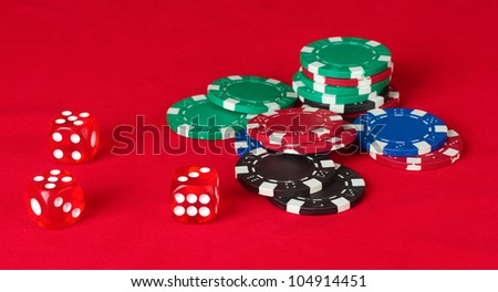 Poker chips wirh dice on a red table