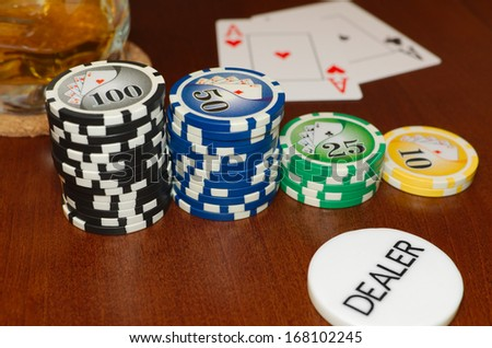 Poker Dealer Button and Casino Tokens with a Pair of Aces and a Cool Drink - stock photo