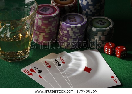 Poker/Four cards, glass of whiskey and chips,dices on poker table