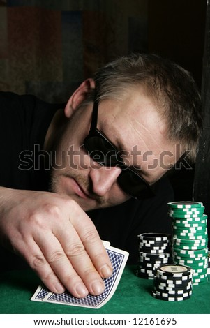 Poker gambler with sun glasses close-up. Focus on the hand and chips. - stock photo