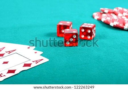 Poker gambling chips, dices and few aces on a green playing table, stacks of poker chips , casino concept - stock photo