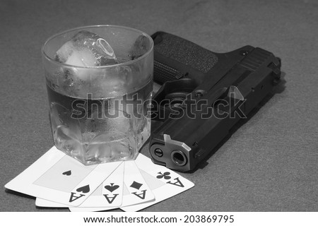 poker hand of aces, card game with drink and a gun like a gangster - stock photo