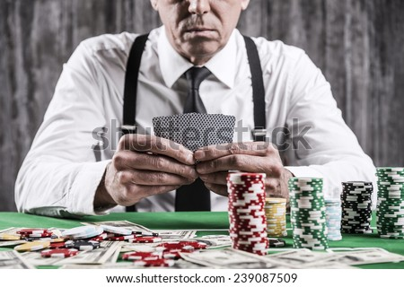 Poker player. Close-up of serious senior man in shirt and suspenders sitting at the poker table and holding cards  with money and  gambling chips laying all around him - stock photo
