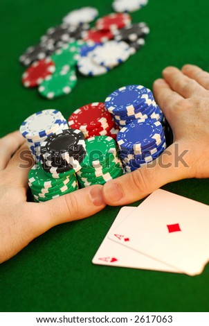 """Poker player going """"all in"""" pushing his chips forward - stock photo"""