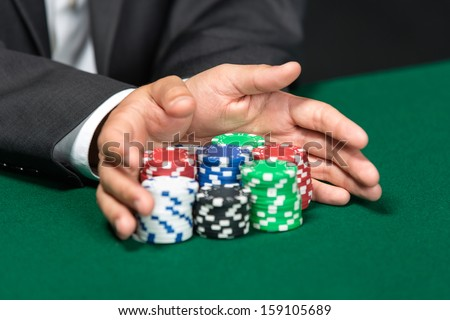 "Poker player going ""all in"" pushing his chips forward. Symbol of addiction to the poker - stock photo"