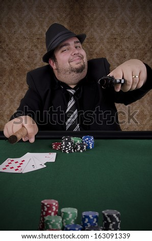 Poker player looking at camera and pointing gun. - stock photo