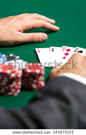 Poker player opens his cards. Risky entertainment of gambling