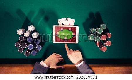 Poker player's hands with digital tablet, stacks of chips and cards on green table, top view - stock photo
