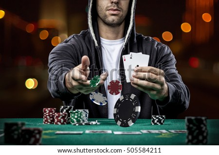 Poker player showing a pair of aces, on a bokeh lights background.