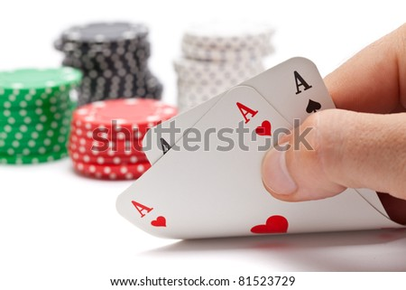 Poker: player shows pocket aces with poker chips in the back on white background - stock photo