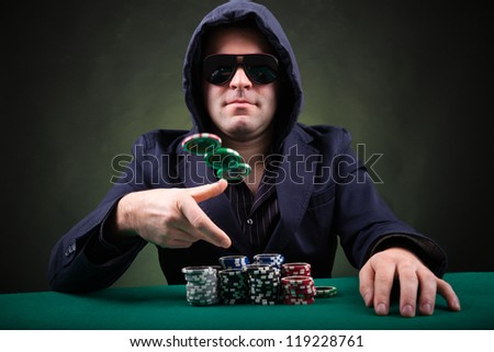 Poker player throwing poker chips on black background - stock photo