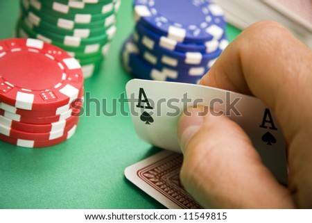 Poker player turning over an ace in his hand
