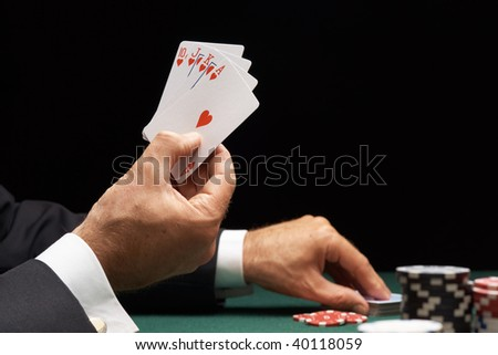 Poker player winning hand of cards royal flush with casino chips - stock photo