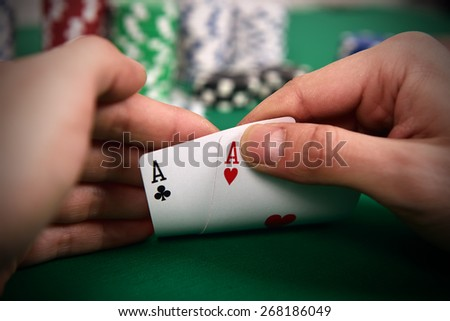 poker player with two Aces and chips at green casino table - stock photo