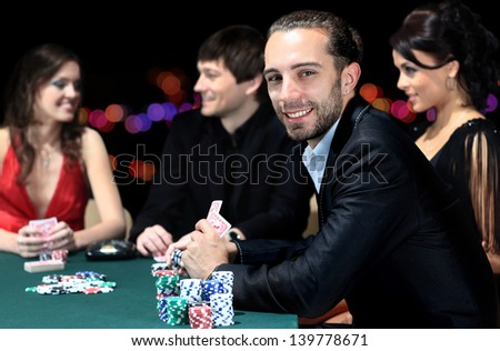 Poker players sitting around a table at a casino - stock photo