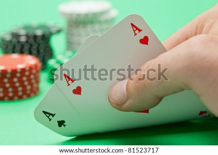 Pokerplayer shows pocket aces with poker chips in the back over green background - stock photo