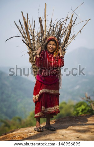 POKHARA, NEPAL - APRIL 28: Nepalese woman in national clothes with basket in Pokhara, Nepal on April 28, 2013. Due to its proximity to the Annapurna mountain range, Pokhara is a base for trekkers.