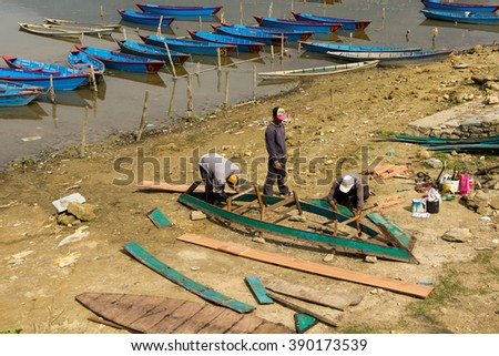 POKHARA, NEPAL - MARCH 11, 2016: Local boatmen repair a wooden boat.