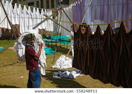 POKHARA, NEPAL - NOVEMBER 11: Unidentified Nepalese men hang out the wash to dry on the clothesline outdoors on November 11, 2013 in Pokhara.