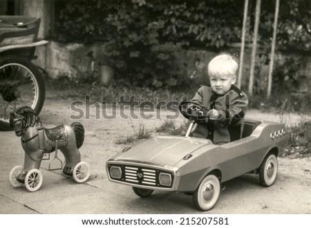 POLAND, CIRCA eighties: Vintage photo of little boy in toy car - stock photo