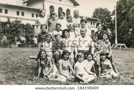 POLAND, CIRCA 1970's: Vintage photo of group of  young girls and teachers posing together  during a summer camp - stock photo