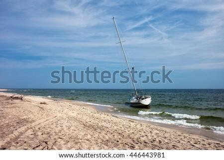Poland, Pomerania, Hel Peninsula, Baltic Sea, lonely sail boat moored at empty beach, solitude in nature - stock photo