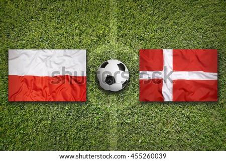 Poland vs. Denmark flags on green soccer field - stock photo