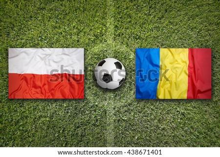 Poland vs. Romania flags on green soccer field - stock photo