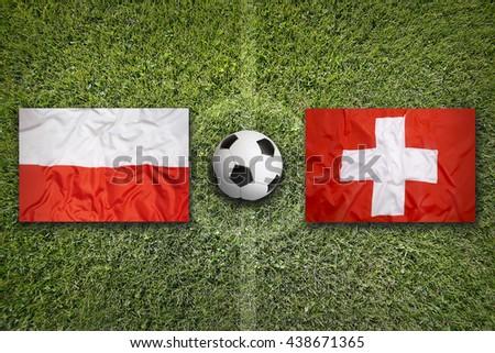 Poland vs. Switzerland flags on green soccer field - stock photo