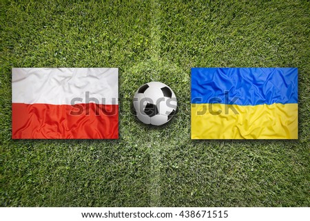 Poland vs. Ukraine flags on green soccer field - stock photo