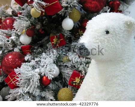 Polar bear next to a beautiful flocked Christmas tree decorated with ornaments and presents