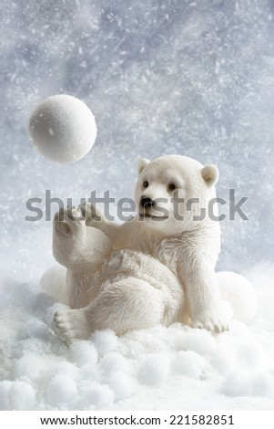 Polar bear winter decoration playing with a snowball - stock photo