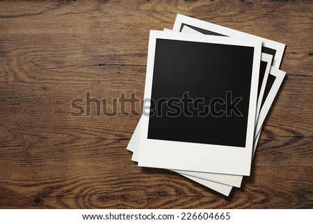 Polaroid photo frames on old wooden background - stock photo