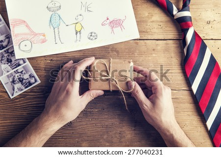 Polaroid pictures of father and daughter, childs drawing, present and tie laid on wooden desk backround. - stock photo