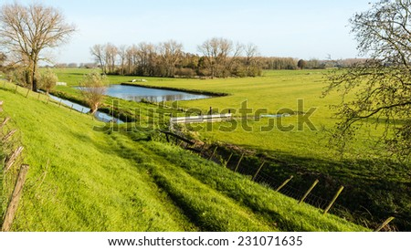 Polder landscape in the Netherlands with blue reflecting water surfaces and trees seen from the dike. - stock photo