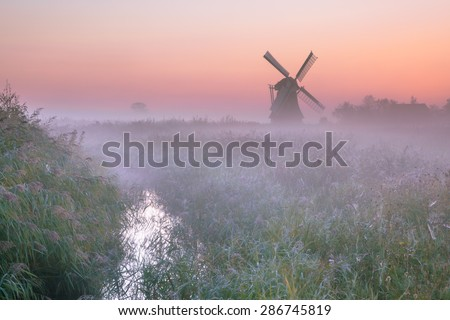 Polder landscape with Characteristic traditional windmill on a foggy september morning in the Netherlands
