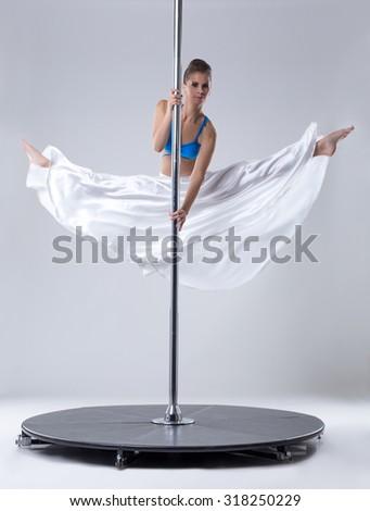 Pole dance. Flexible woman posing in split - stock photo