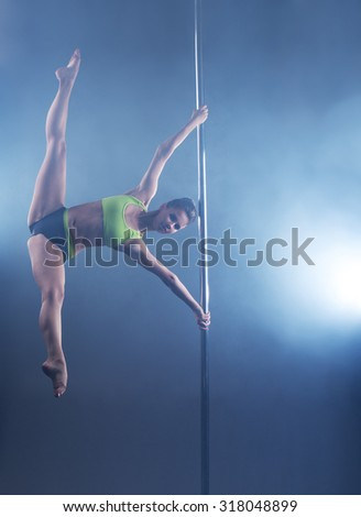 Pole dance. Strong girl froze in stretching pose - stock photo